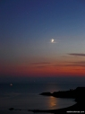 Celestial triangle and crescent Moon over Isola d'Elba